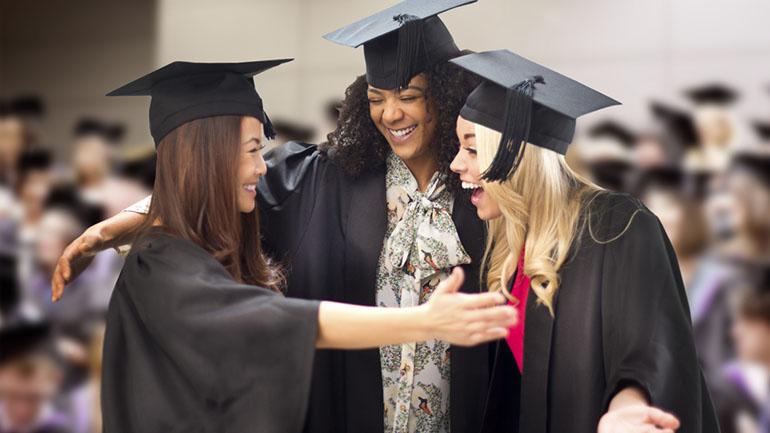 three friends hug at their graduation